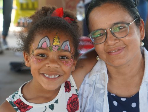 Mother and daughter with unicorn face paint smiling